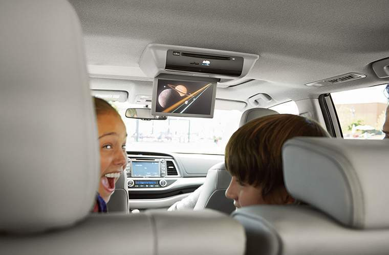 Two happy children inside 2018 Toyota Highlander with Rear Seat Entertainment System highlighted