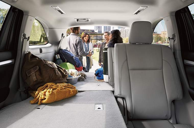 Group of people storing cargo inside 2018 Toyota Highlander with split folding rear seats shown