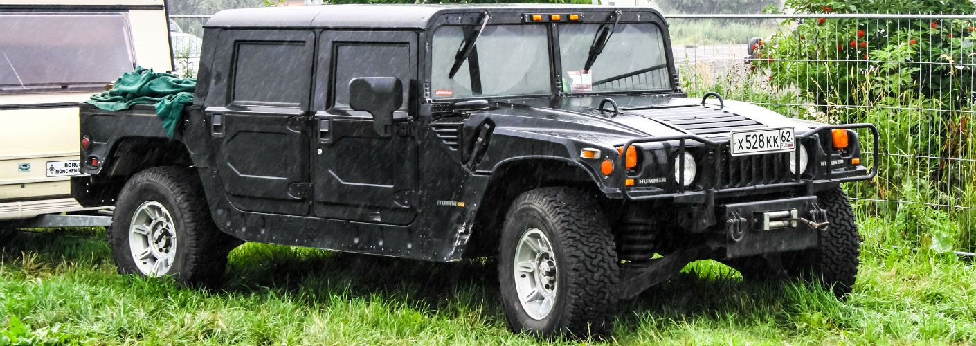 Hummer Parked in Field Towing Trailer