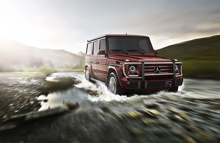 red Mercedes-Benz G-Class crossing a river