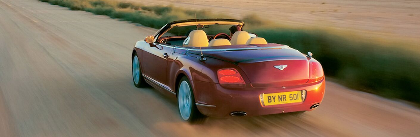 red bentley convertible on dirt road