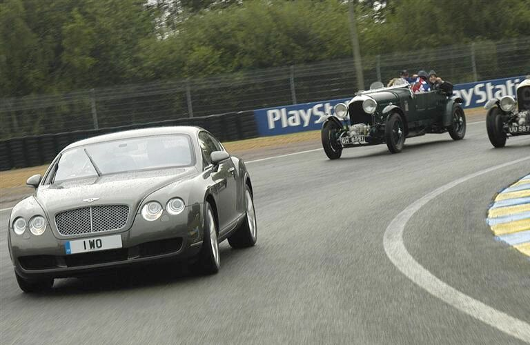 2009 bentley continental on racetrack with antique cars