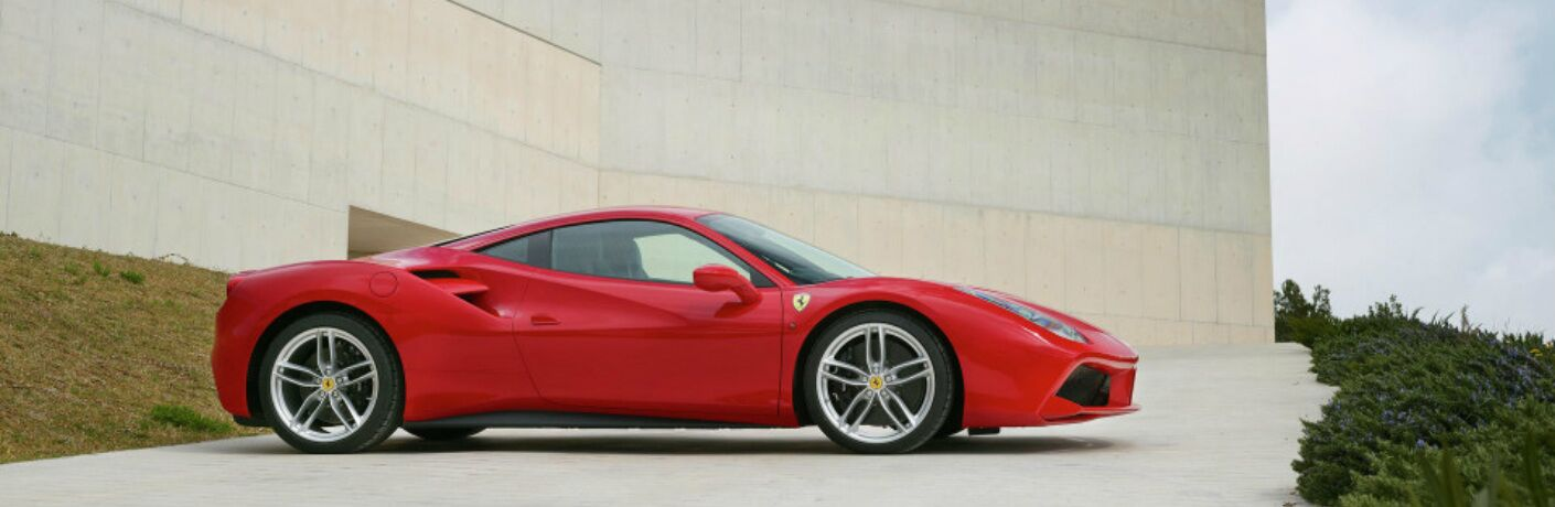 red ferrari 488 parked outside a building