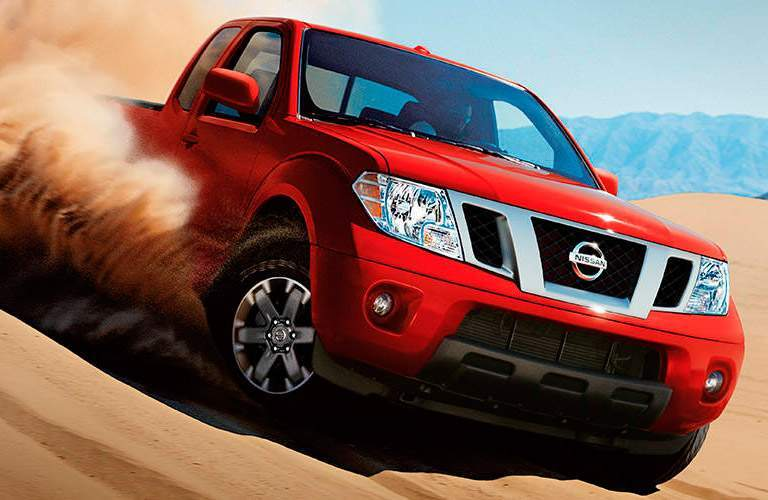 red 2017 Nissan Frontier driving through sand