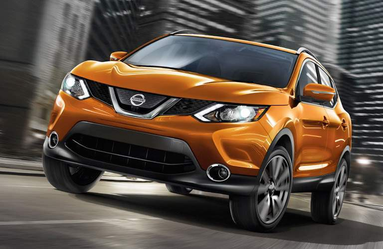 orange 2017 Nissan Rogue Sport driving through city exterior front view