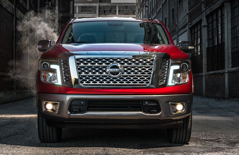 View of red 2018 Nissan TITAN parked in an alley showing off a close shot of the grill