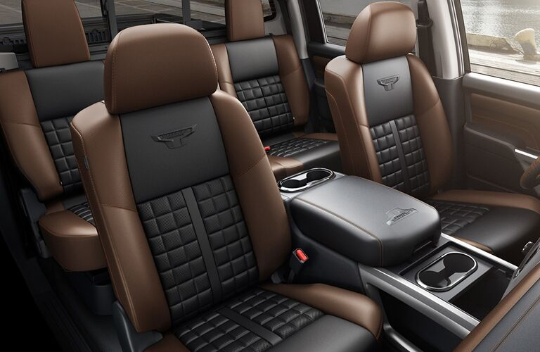 View of 2018 Nissan TITAN interior showing black and brown seating in front and back