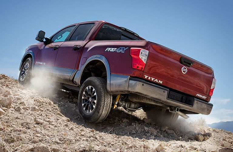 View of red 2018 Nissan TITAN scaling off-road terrain during the day