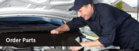 happy mechanic working under hood of car