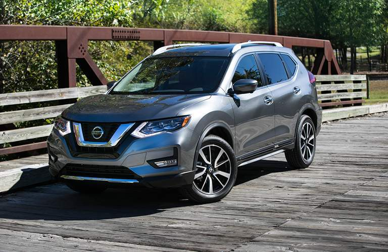 Front Quarter profile of the 2018 Nissan Rogue parked on a bridge surrounded by trees