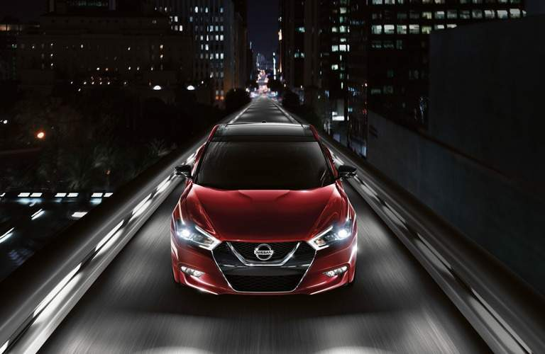 2018 Red Nissan Maxima front view of car driving down city street at night
