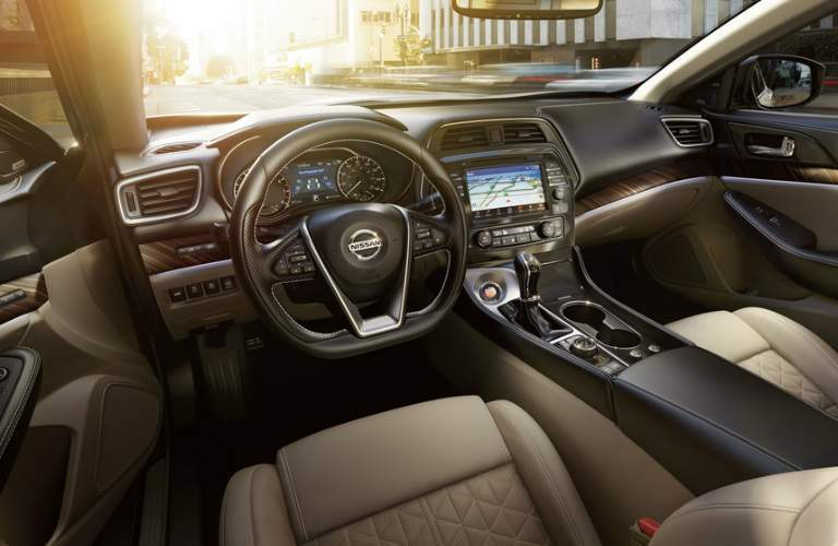 2018 Nissan Maxima interior view of tan seating and black steering wheel and infotainment touch screen