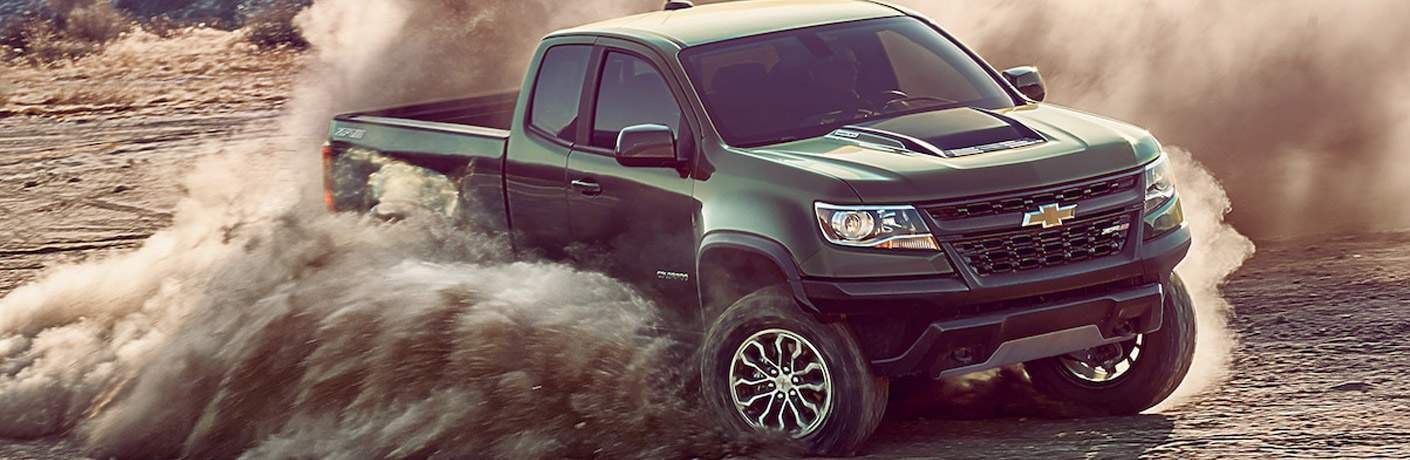 Chevrolet Colorado pickup driving through sand and kicking up dust