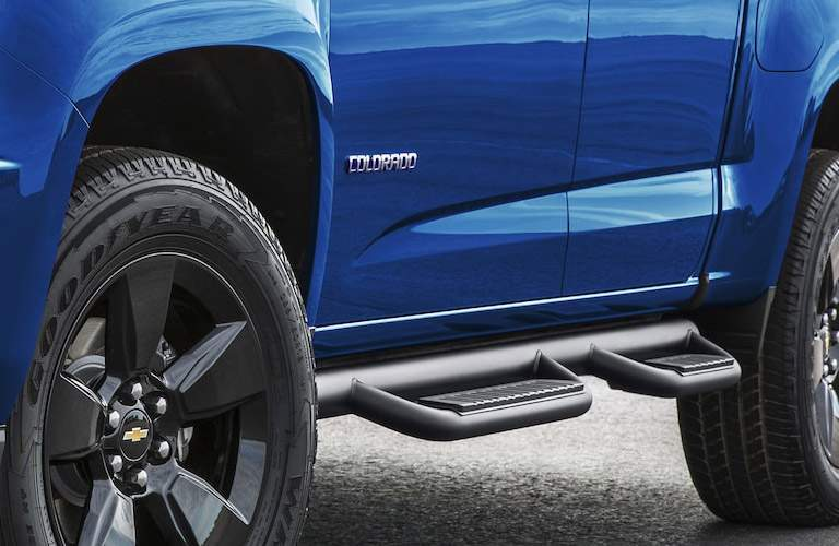 Side shot of blue Chevrolet Colorado with tires and kickplate visible