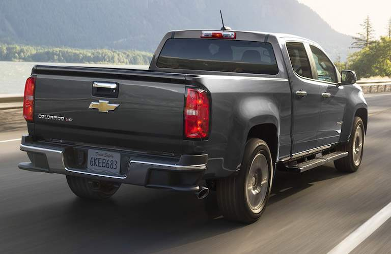 Black Chevrolet Colorado truck driving down empty mountain road