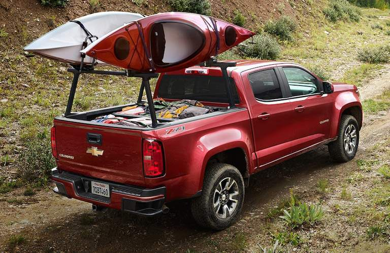 Red Chevrolet Colorado hauling canoes down dirt trail