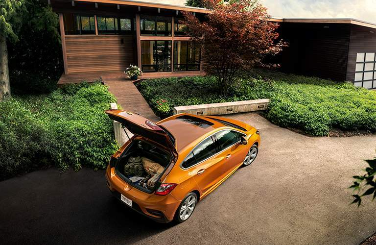 Chevrolet Cruze parked in front of modern home with rear hatch opened to cargo space