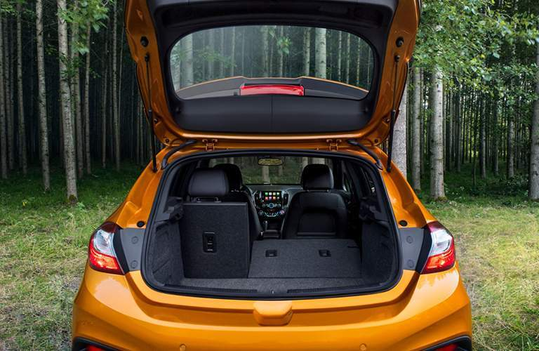 Rear liftgate of 2018 Chevrolet Cruze opened to show interior space and seats folded down