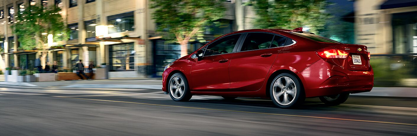 2019 Chevrolet Cruze exterior side shot with red paint color driving through a city a night with the background blurring