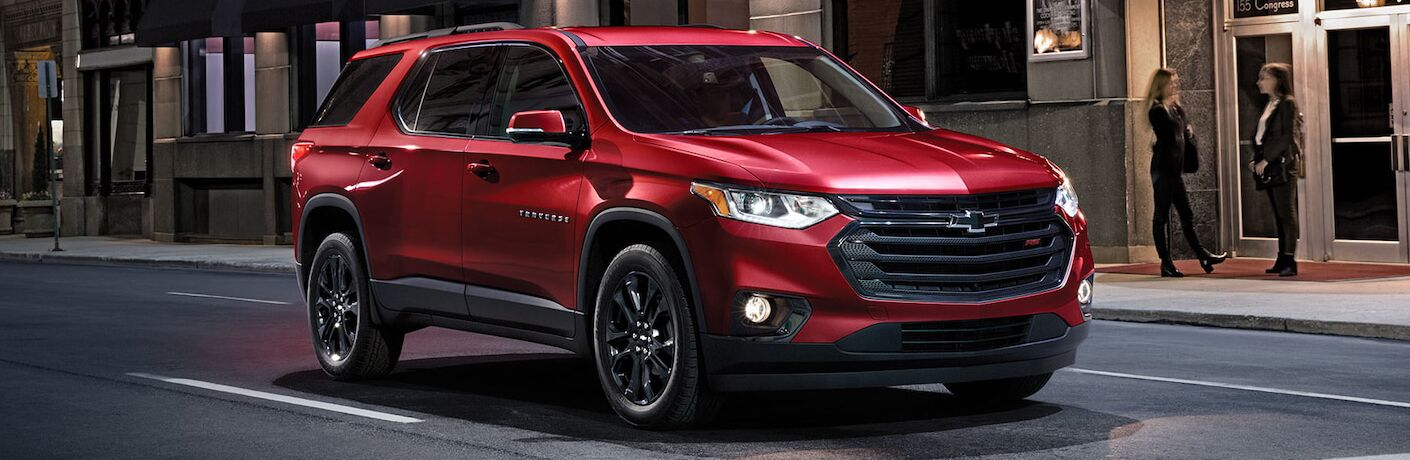 2019 Chevrolet Traverse exterior shot with red paint color driving through a city at night as two women talk outside a building