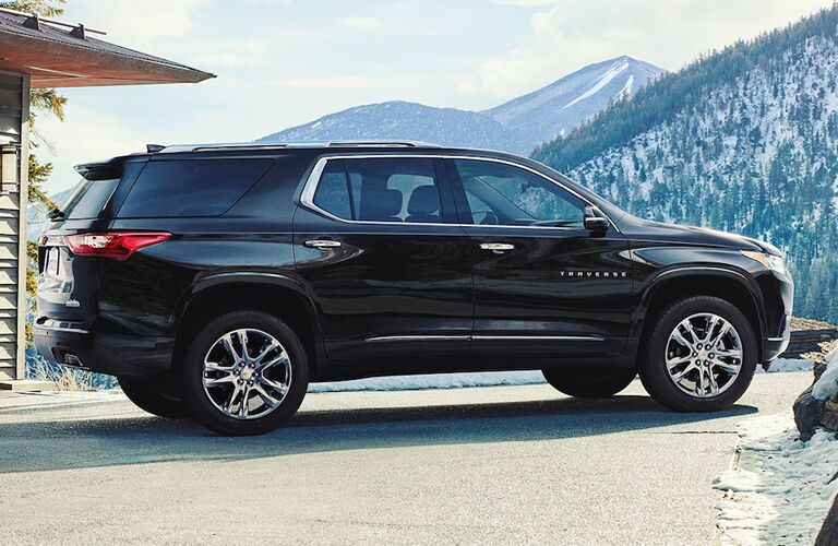 2019 Chevrolet Traverse exterior side shot with black paint color parked outside a fancy mountain house with snowy, forest filled mountains in the background