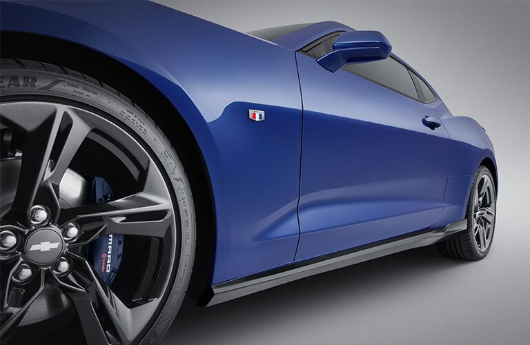 2019 Chevy Camaro low exterior shot closeup of tires, wheel badges, and body frame with blue paint color