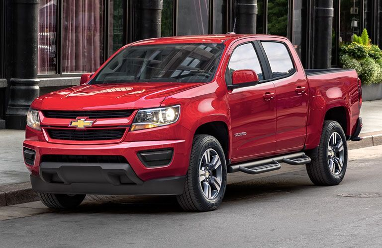 2019 Chevy Colorado exterior shot with red paint color parked on the side of a street in the daytime