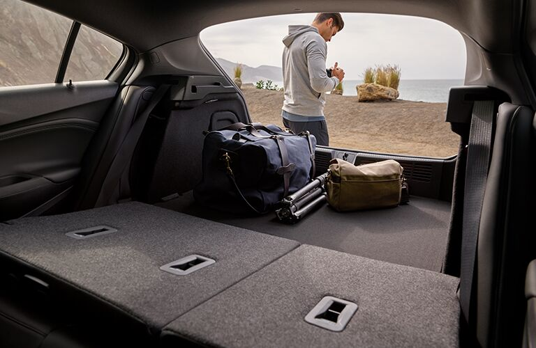 2019 Chevrolet Cruze interior shot of adjustable cargo capacity looking out as driver loads cargo near a beach