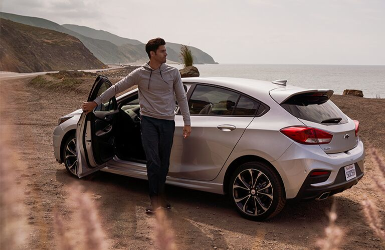 2019 Chevrolet Cruze exterior side shot with gray silver paint color with the driver exiting the vehicle onto a dirt desert landscape