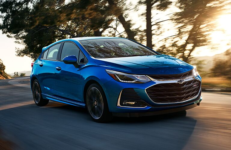 2019 Chevrolet Cruze exterior shot with blue paint color driving near sparse trees