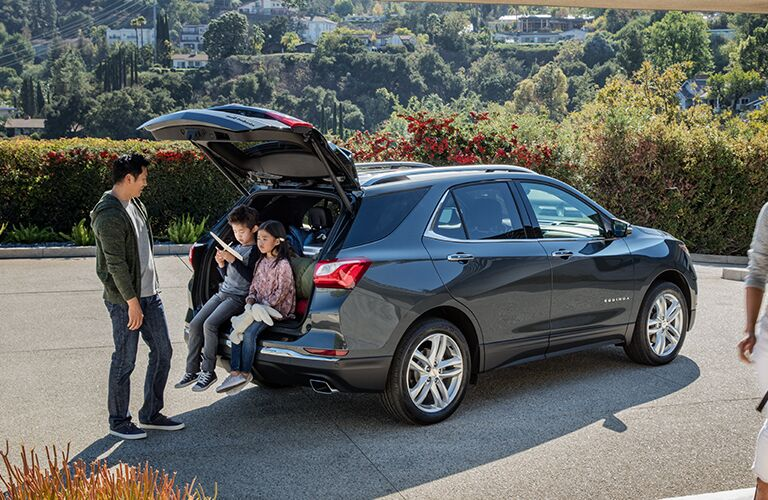 Rear liftgate of 2019 Chevrolet Equinox opened with kids sitting in rear cargo area