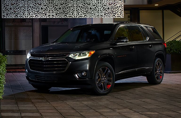 2019 Chevrolet Traverse exterior shot with black paint color and headlights on parked outside an apartment building