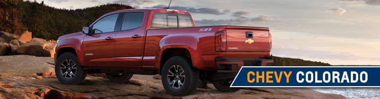 Red Chevrolet Colorado parked on beach with trees in distance