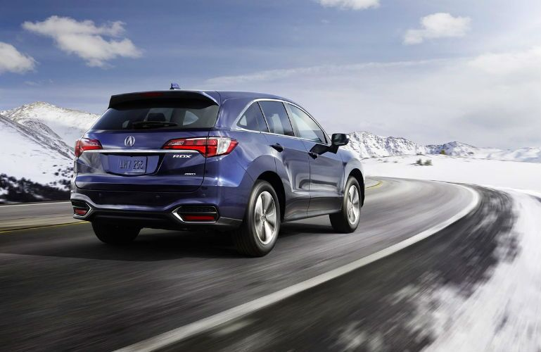 2018 Acura RDX AWD in Fathom Blue Pearl driving through snowy landscape