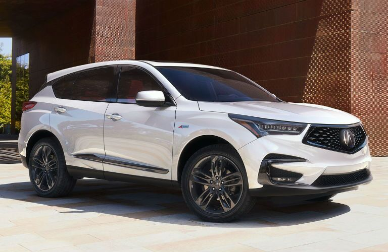 2019 Acura RDX with A-Spec Package in White Diamond Pearl parked by a brick building