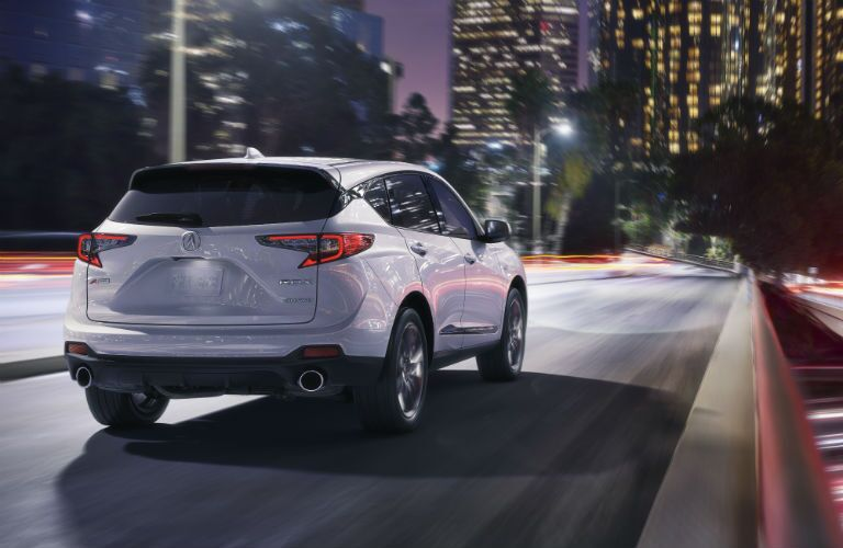 2019 Acura RDX driving toward a city at night