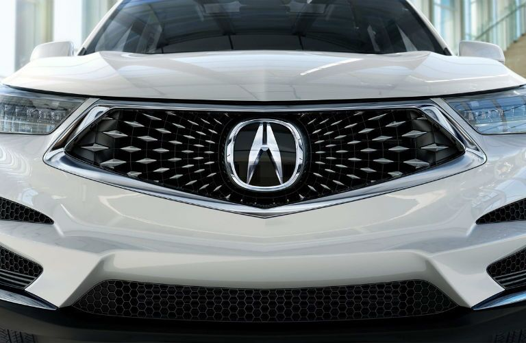 2019 Acura RDX in White Diamond Pearl with a close-up of the Diamond Pentagon grille