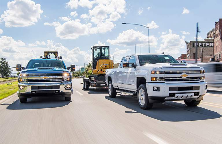 Two 2018 Chevy Silverado 2500HD trucks towing trailers