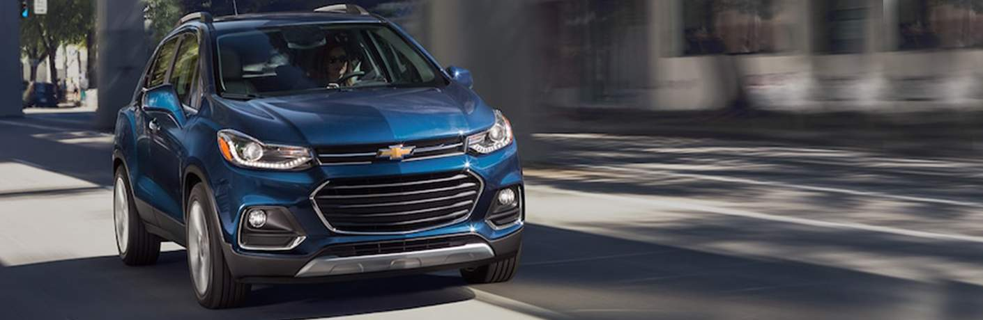 Person driving the 2018 Chevrolet Trax down the road in a city with building blurring past