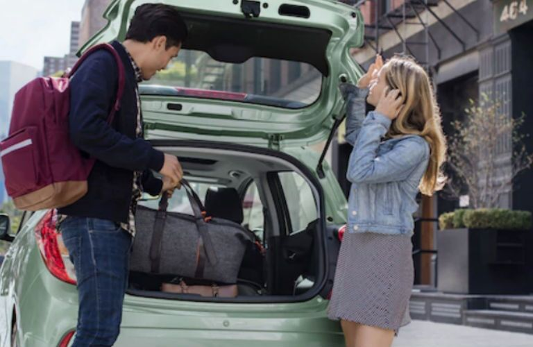 2018 Chevy Spark with rear hatch open and couple taking luggage out of it