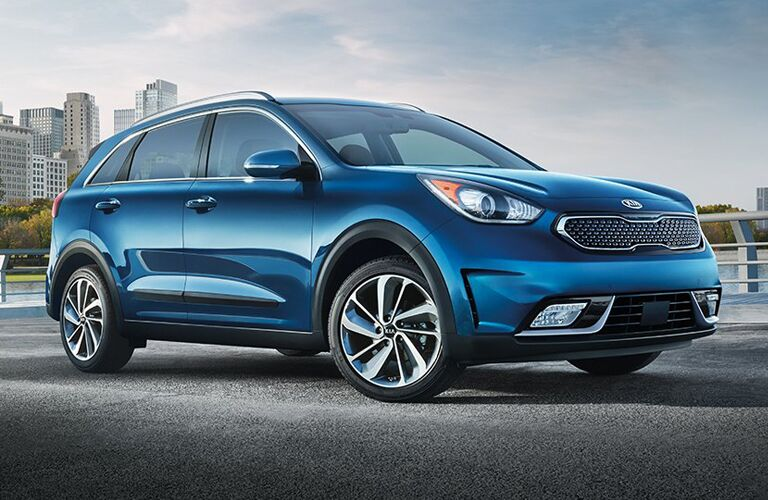 Exterior view of a blue 2018 Kia Niro parked near a body of water in the city