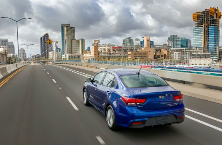 Exterior view of the rear of a blue 2018 Kia Rio driving down an expressway in the city
