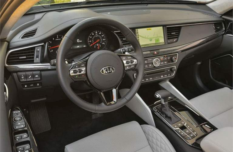Interior view of a black steering wheel and touchscreen in a 2018 Kia Cadenza