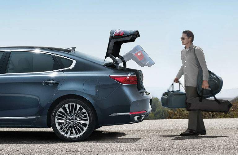 Exterior view of a blue 2018 Kia Cadenza with a man placing luggage into the open trunk