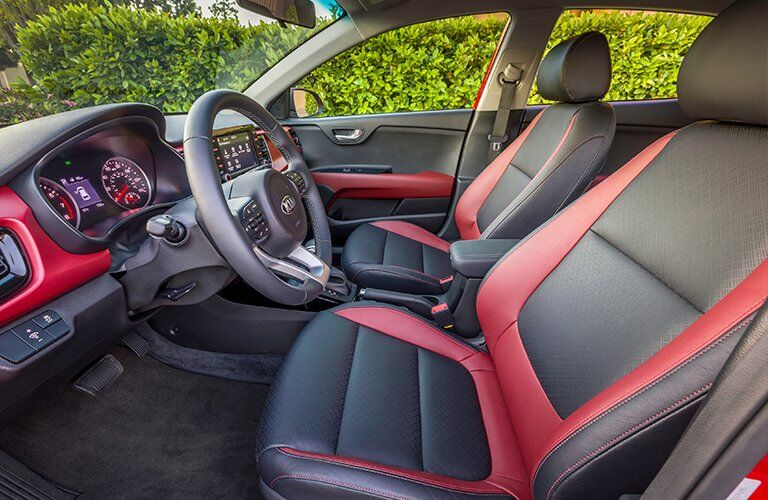 Interior view of the black front seats with red trim inside a 2018 Kia Rio