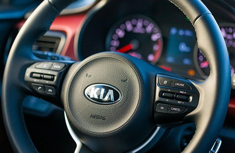 Closeup interior view of the black steering wheel of a 2018 Kia Rio