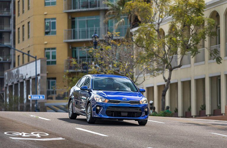 Exterior view of the front of a blue 2018 Kia Rio driving down a city street