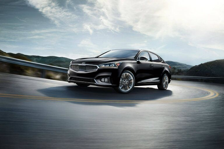 Exterior view of a black 2019 Kia Cadenza driving around a curve on a two-lane highway