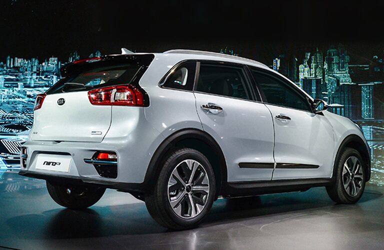 Exterior view of the rear of a white 2019 Kia Niro parked in a show room with a digital city skyline in the background