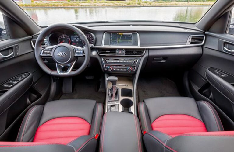 Interior view of the black steering wheel, touchscreen, and black and red seating inside a 2019 Kia Optima